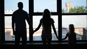 Silhouette of family holding hands by the window stock video