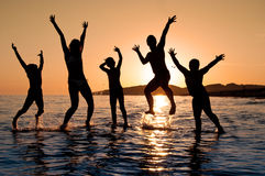 Silhouette of family jumping. On the beach on beautiful summer sunset Stock Photography