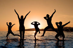 Silhouette of family jumping. On the beach on beautiful summer sunset Royalty Free Stock Photography