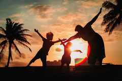 Silhouette of family with kids play at sunset beach. Silhouette of family with kids play at sunset tropical beach royalty free stock image