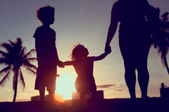 Silhouette of family with kids play at sunset beach royalty free stock photography