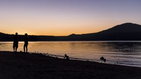 Silhouette of Family at a Lake royalty free stock images