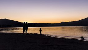 Silhouette of Family at a Lake stock images