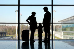 Silhouette of family with luggage near window Stock Photos
