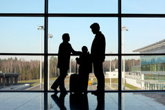 Silhouette of family with luggage near window Stock Photo