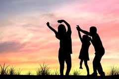 Silhouette of family, mom and dad, parents. Take daughter or girl dancing in sunset because They have free time, relax and have funny and happy day royalty free stock photo
