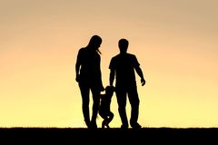 Silhouette of Family of Three People Walking at Sunset Stock Images