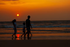 Silhouette of family walking along the coast stock images