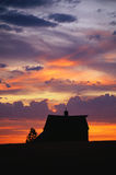 Silhouette of a farm at sunset Stock Image