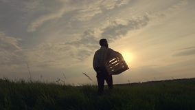 Silhouette of a farmer with a box stock footage