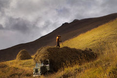 Silhouette of farmer with a pitchfork collecting hay Royalty Free Stock Photos