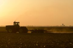 Silhouette of farmer tilling his land after the harvest. Royalty Free Stock Photography