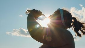 Silhouette of a fat girl drinks water from a bottle. After a workout outdoors against sun rays and blue sky stock video