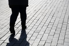 Silhouette of fat woman walking down the street, black shadow on pavement. Thick legs in jeans, concept of overweight, diet, loneliness, dramatic life story stock image
