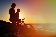 Silhouette of father and baby biking at sunset Stock Image
