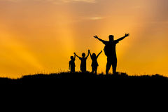 Silhouette father and children standing raised hands up on sunset Stock Photo