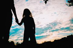 Silhouette of father and daughter holding hands at sunset. Nature stock photos