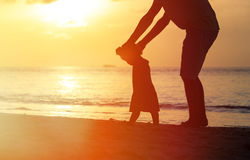 Silhouette of father and daughter learning to walk. Silhouette of father and little daughter learning to walk at sunset beach Stock Photos