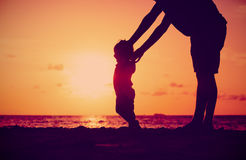 Silhouette of father and daughter learning to walk at sunset Royalty Free Stock Photography