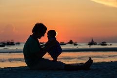 Silhouette of father and daughter on sunset beach Royalty Free Stock Photo