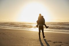 Silhouette Of Father Giving Son Piggyback On Winter Beach royalty free stock images