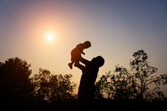 Silhouette of father with her toddler against the sunset Royalty Free Stock Photos