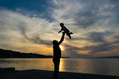 Silhouette of a father and his son against the sunset with a dramatic sky. Stock Photography