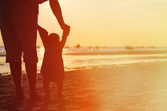 Silhouette of father and little daughter at sunset stock photography