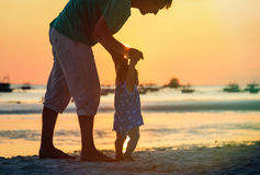 Silhouette of father and little daughter on sunset beach Royalty Free Stock Photo