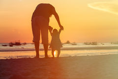 Silhouette of father and little daughter walk at sunset Stock Image
