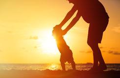 Silhouette of father and little daughter walk at sunset stock images