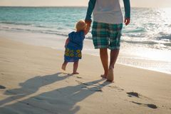 Silhouette of father and little daughter walk at sunset. Beach Stock Photography
