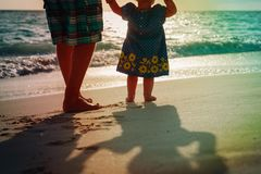 Silhouette of father and little daughter walk at sunset. Beach Royalty Free Stock Image