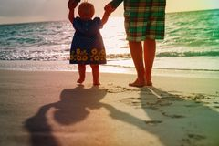 Silhouette of father and little daughter walk at sunset. Beach Stock Image