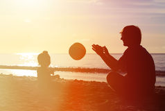 Silhouette of father and little daugther play ball. On sunset beach royalty free stock photography