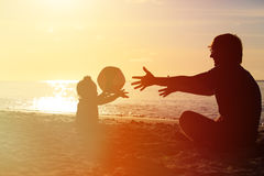 Silhouette of father and little daugther play ball at sunset Stock Photos