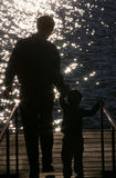 Silhouette of a Father and Son. Father and Son holding hands while walking down a dock towards a sparkling lake Stock Image