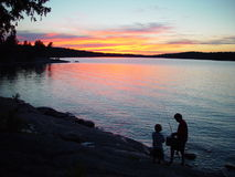 Silhouette of father and son fishing. At sunset royalty free stock photos