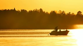Silhouette of father and son fishing on lake. Irving as sun sets in Bemidji, Minnesota
