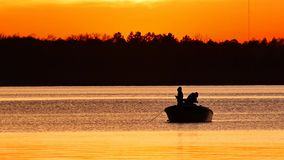 Silhouette of father and son fishing on lake. Irving at sunset in Bemidji, Minnesota