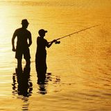 Silhouette of father and son fishing at sunset. Silhouette of father and son fishing rod at sunset reflection on water wading to knees Royalty Free Stock Images