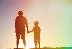 Silhouette of father and son holding hands at sunset Stock Image