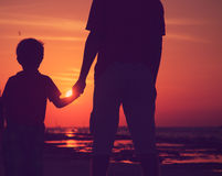 Silhouette of father and son holding hands at sunset sea Stock Photos