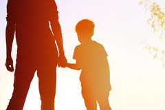 Silhouette of father and son holding hands at sunset Stock Photography