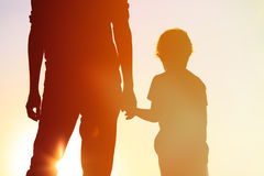 Silhouette of father and son holding hands at sunset. Sky Stock Images