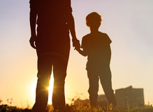 Silhouette of father and son holding hands at sunset Stock Images