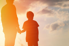 Silhouette of father and son holding hands at sunset. Sky Stock Photos
