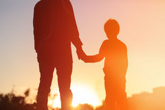 Silhouette of father and son holding hands at sunset Royalty Free Stock Photography