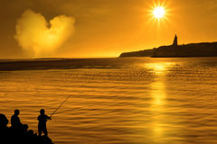 Silhouette of father and son loving fishing Stock Photography