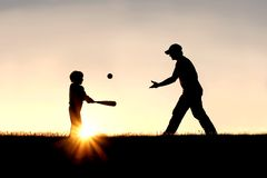 Silhouette of Father and Son Playing Baseball Outside. A silhouette of a father and his young child playing baseball outside, against the sunsetting sky on a royalty free stock images
